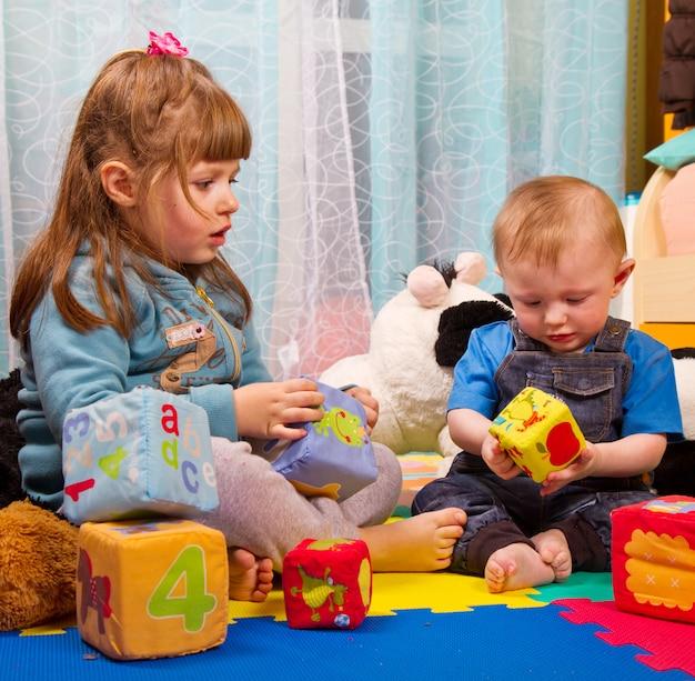 Bruder und schwester, die mit weichem farbigem würfel spielen