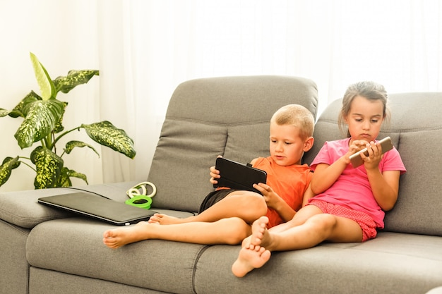 Bruder und schwester, die zu hause auf couch unter verwendung des handys sitzen. schließen sie herauf die überraschte tochter und frustrierten sohn, die gerätbildschirm betrachten. technologie neue generation mit gadgets süchtig