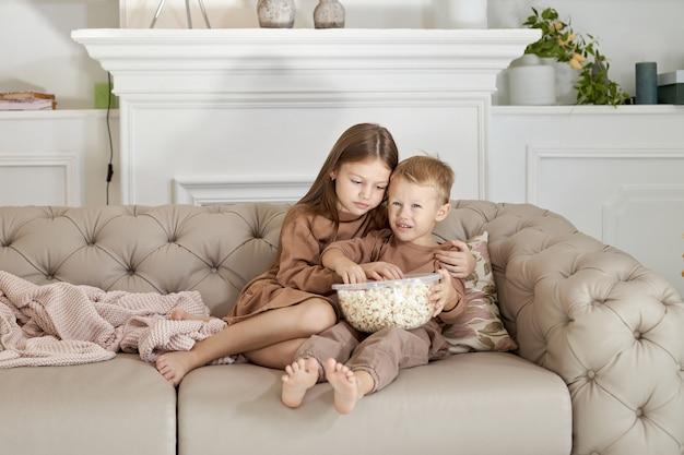Bruder und schwester essen popcorn, das zu hause auf der couch sitzt. ein junge und ein mädchen entspannen sich, haben spaß und schauen sich einen film im fernsehen an