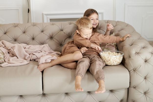 Bruder und schwester essen popcorn, das zu hause auf der couch sitzt.