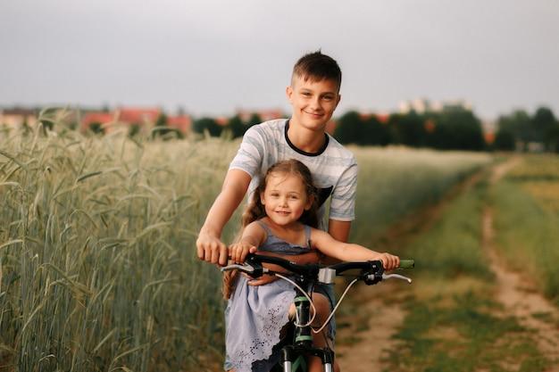 Bruder und schwester fahren fahrrad auf einem weizenfeld