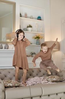 Bruder und schwester haben spaß zu hause und springen auf die couch