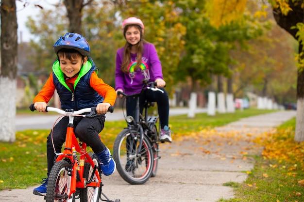 Bruder und schwester im park. der junge fährt fahrrad. mädchen, das in der wand lächelt. foto mit seitenraum.