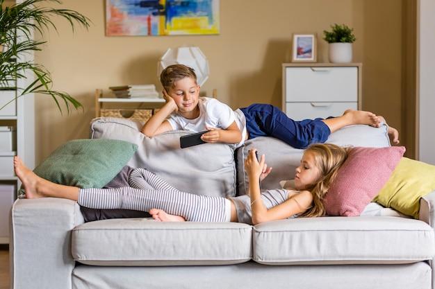 Bruder und schwester im wohnzimmer sitzen auf der couch