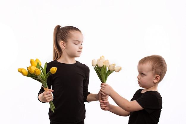 Bruder und schwester in den schwarzen blusen, die tulpen in ihren händen halten