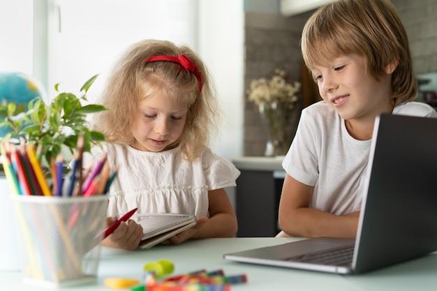 Bruder und schwester lernen zu hause an laptop-kindern und -geräten