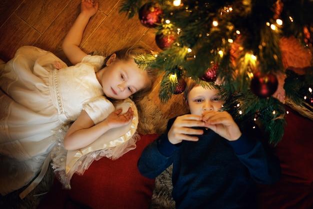 Bruder und schwester liegen auf dem teppich in der nähe des neujahrsbaums im gemütlichen weihnachtsinterieur