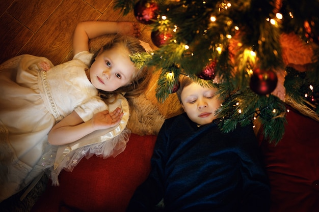 Bruder und schwester liegen auf dem teppich in der nähe des weihnachtsbaums im gemütlichen weihnachtsinterieur