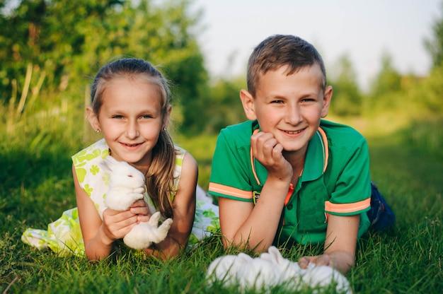 Bruder und schwester liegen mit kleinen kaninchen im gras. osterhase
