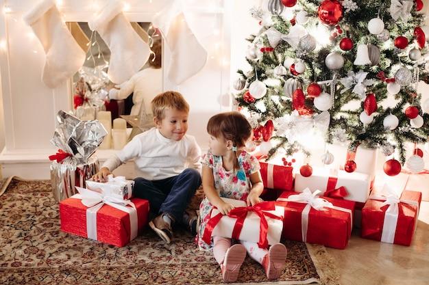 Bruder und schwester öffnen weihnachtsgeschenke