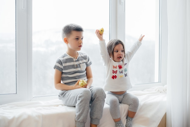 Bruder und schwester sitzen auf der fensterbank und essen und essen äpfel. glück