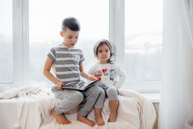 Bruder und schwester sitzen auf der fensterbank und lesen ein buch. glück, familie