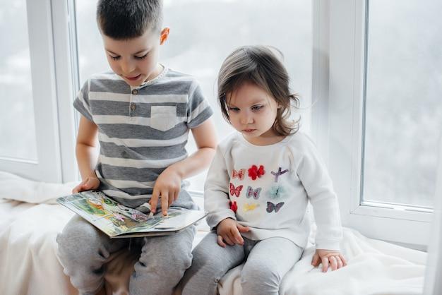 Bruder und schwester sitzen auf der fensterbank und lesen ein buch. glück, familie.
