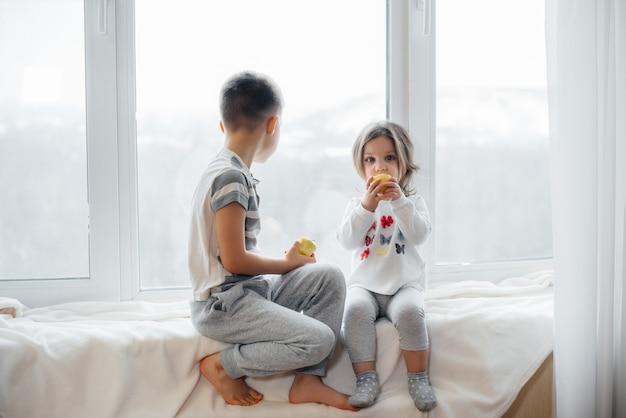Bruder und schwester sitzen auf der fensterbank und spielen und essen äpfel. glück.