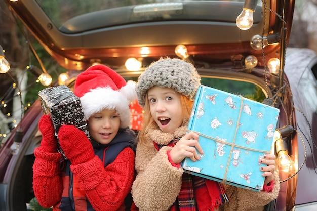 Bruder und schwester sitzen im mit silvester geschmückten auto mit vielen geschenkboxen