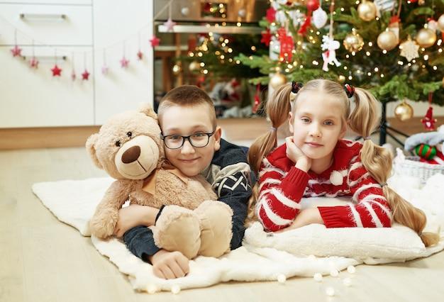 Bruder und schwester sitzen in der nähe von weihnachtsbaum mit plüschtieren