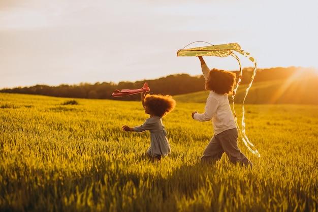 Bruder und schwester spielen mit drachen und flugzeug auf dem feld bei sonnenuntergang