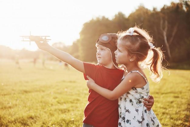 Bruder und schwester spielen zusammen. zwei kinder, die mit einem hölzernen flugzeug im freien spielen