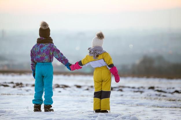 Bruder und schwester stehen draußen auf schneebedecktem winterfeld, das hände hält