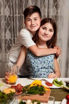 Bruder und schwester umarmten sich am esstisch