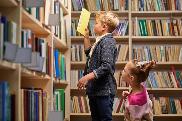 Bruder und schwester wählen bücher in der bibliothek, unterhalten sich, in der schulbibliothek