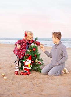 Bruder und seine kleine schwester schmücken den weihnachtsbaum am strand.