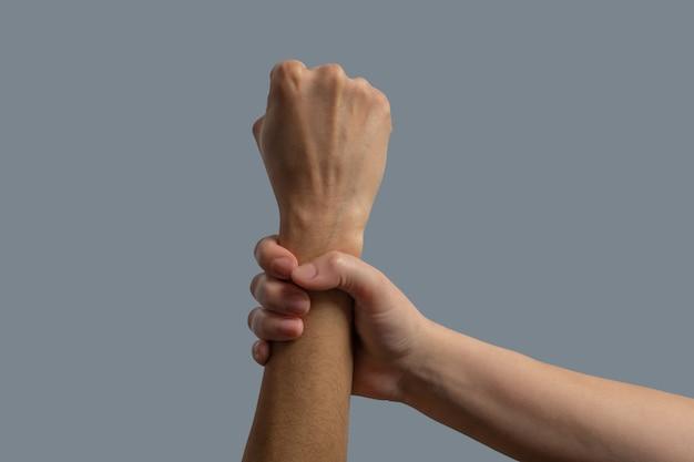 Bruderschaft der menschheit. nahaufnahme der hellhäutigen hand, die das dunkelhäutige handgelenk zusammenpreßt