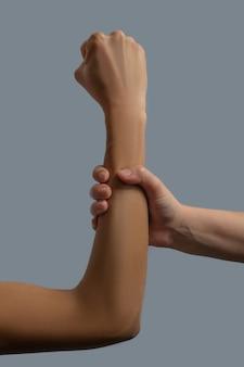Bruderschaft der menschheit. nahaufnahme der hellhäutigen hand, die den dunkelhäutigen unterarm zusammenpreßt