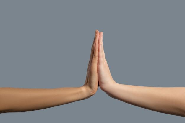Bruderschaft der menschheit. nahaufnahme von menschen verschiedener rassen, die palmen zusammenhalten