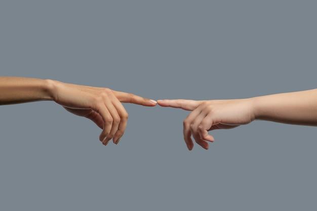 Bruderschaft der menschheit. nahaufnahme von menschen verschiedener rassen, die zwei zeigefinger zusammen berühren