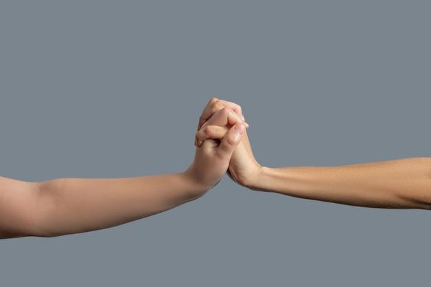 Bruderschaft. nahaufnahme von hellhäutigen und dunkelhäutigen händen zusammengepresst
