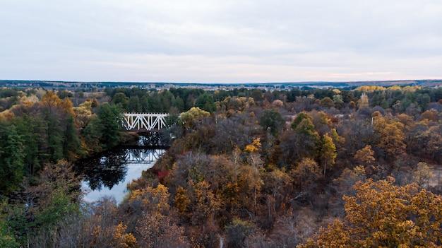 Brücke über einen fluss zwischen reservierten herbstwäldern, entlang denen die eisenbahn fährt.