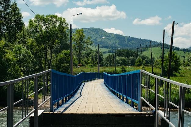 Brücke über gebirgsfluss zwischen den hügeln auf bergen unter blauem himmel