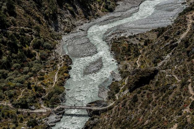 Brücke und fluss mit einer person kreuzen ein in der everest-regionsstraße in nepal.