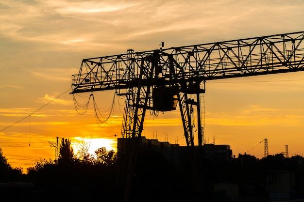 Brückenkran am bahnhof. kranschattenbild auf sonnenunterganghintergrund. schwerindustrie-konzept.