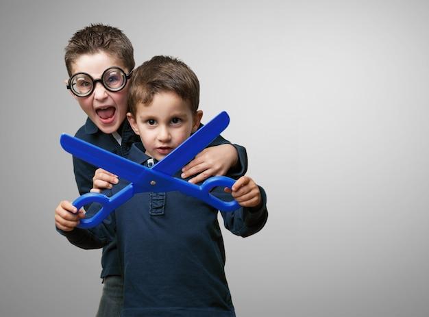 Brüder, die mit kunststoff schere spielen