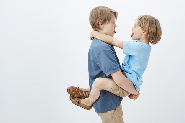 Brüder finden immer einen weg, gemeinsam spaß zu haben. sorglose süße männliche geschwister, die sich gegenseitig die zunge zeigen und sich umarmen