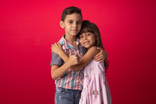 Brüder-kind, das im studiofoto mit rotem hintergrund lächelt und umarmt.
