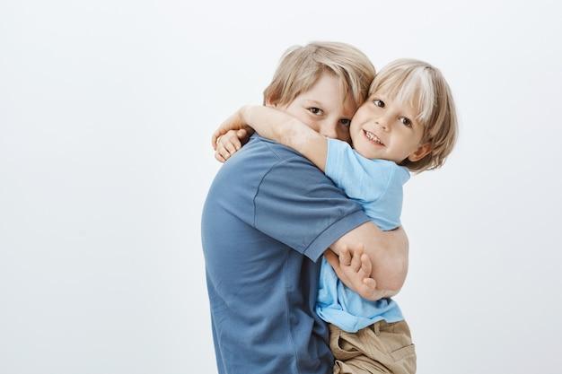 Brüder sind beste freunde. porträt des niedlichen europäischen jungen, der bruder umarmt und schaut und glücklich ist, geschwister zu haben