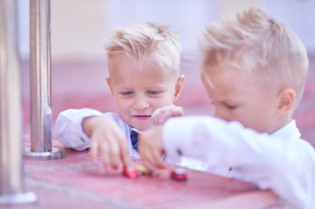 Brüder spielen mit spielzeugautos in der nähe der schule