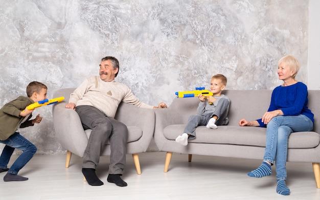 Brüder spielen mit waffen und rennen im wohnzimmer um großeltern herum