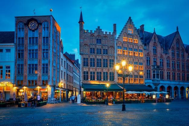 Brügge grote marktplatz mit café und restaurants in der abenddämmerung
