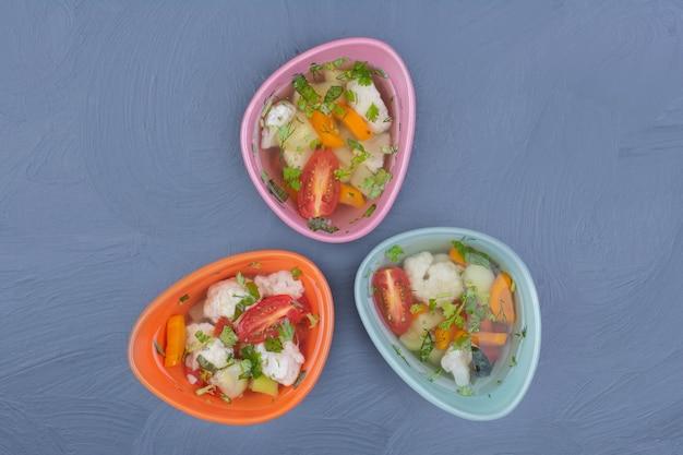 Brühe suppe in mehrfarbigen tassen mit gehacktem gemüse
