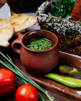 Brühensuppe mit kräutern und gemüse in einem tonwarenglas.