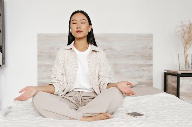 Brünette asiatin mit kopfhörern meditiert im schlafzimmer