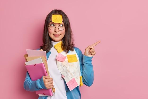 Brünette asiatische managerin untersucht papierdokumente punkte weg auf leerzeichen arbeitet am startup-projekt.