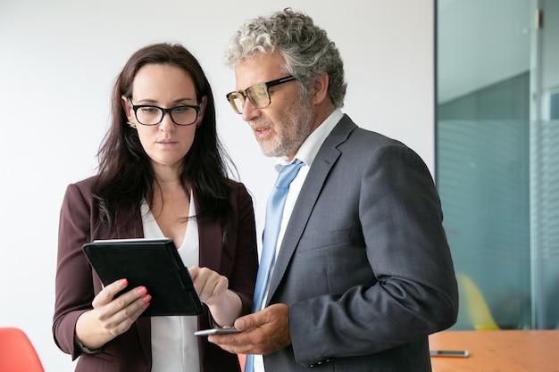 Brünette assistentin zeigt daten zum chef und hält tablette