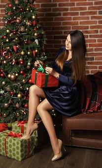 Brünette erwachsene frau, die kleid öffnet geschenkbox neben geschmücktem weihnachtsbaum