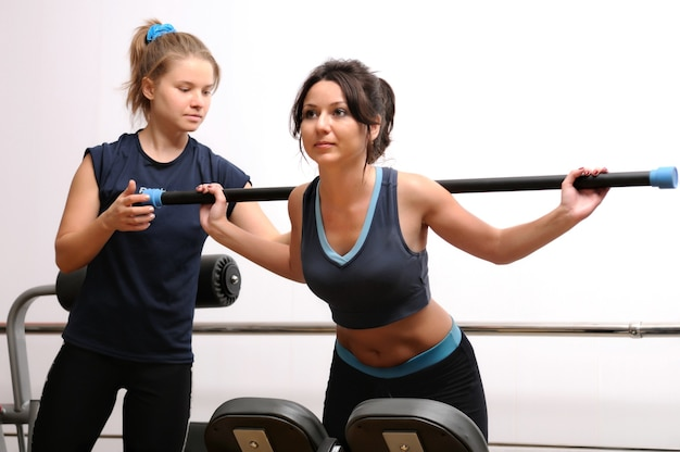 Brünette europäische frau, die körperliche übung mit gymnastikstab auf fitnessgeräten tut. blondes mädchen in sportbekleidung hilft.