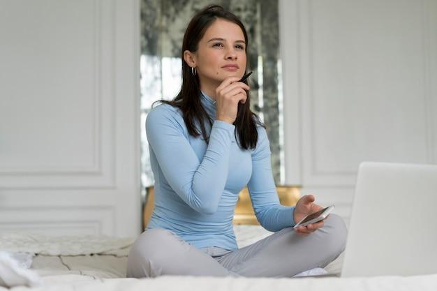 Brünette frau denkt beim sitzen auf dem bett thinking